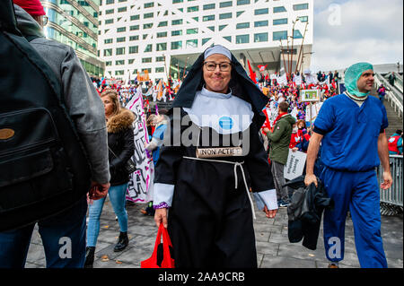 A female hospital worker dressed as a nun during the demonstration.Four trade unions, FNV, FBZ, NU'91 and CNV launched the national campaign to strike over ongoing negotiations with the Dutch Association of Hospitals (NVZ). Thousands of hospital workers gathered at the Jaarbeursplein where Chairman Ad Melkert of the Dutch Association of Hospitals (NVZ) received 37.457 signatures demanding a five percent structural wage increase and extra allowance on wages when employees are called to work last-minute. They also demand agreements concerning heavy staff workloads, as well as the retention of em - Stock Photo