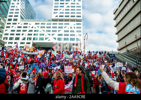 Crowd of hospital workers posing for a pic during the demonstration.Four trade unions, FNV, FBZ, NU'91 and CNV launched the national campaign to strike over ongoing negotiations with the Dutch Association of Hospitals (NVZ). Thousands of hospital workers gathered at the Jaarbeursplein where Chairman Ad Melkert of the Dutch Association of Hospitals (NVZ) received 37.457 signatures demanding a five percent structural wage increase and extra allowance on wages when employees are called to work last-minute. They also demand agreements concerning heavy staff workloads, as well as the retention of e - Stock Photo