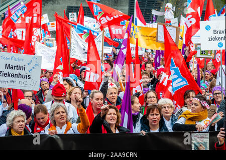 Crowd of hospital workers shouting slogans while holding flags and placards during the demonstration.Four trade unions, FNV, FBZ, NU'91 and CNV launched the national campaign to strike over ongoing negotiations with the Dutch Association of Hospitals (NVZ). Thousands of hospital workers gathered at the Jaarbeursplein where Chairman Ad Melkert of the Dutch Association of Hospitals (NVZ) received 37.457 signatures demanding a five percent structural wage increase and extra allowance on wages when employees are called to work last-minute. They also demand agreements concerning heavy staff workloa - Stock Photo