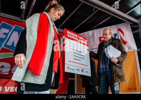 Ad Melkert, chairman of the Dutch Association of Hospitals, receiving signatures on the stage during the demonstration.Four trade unions, FNV, FBZ, NU'91 and CNV launched the national campaign to strike over ongoing negotiations with the Dutch Association of Hospitals (NVZ). Thousands of hospital workers gathered at the Jaarbeursplein where Chairman Ad Melkert of the Dutch Association of Hospitals (NVZ) received 37.457 signatures demanding a five percent structural wage increase and extra allowance on wages when employees are called to work last-minute. They also demand agreements concerning h - Stock Photo