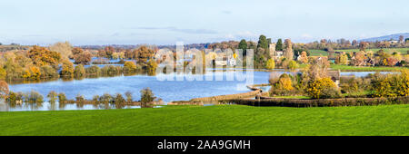 Oddas Chapel and St Marys church viewed across floodwater from the River Severn filling fields around the Severn Vale village of Deerhurst 18/11/2019 - Stock Photo