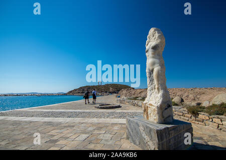naxos, Greece - July 12, 2019: Turists walking by the statue of Ariadne on the promenade leading to Portara, Apollo temple ruins on a sunny day - Stock Photo