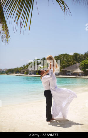 Happy groom holds bride on his hands under wedding ceremony arch on tropical island beach on Maldives. Turquoise ocean lagoon, white sand and - Stock Photo