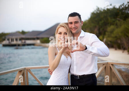 Happy bride and groom smiling and showing the heart sign with their hands on a tropical beach of luxury spa resort on Maldives. Wedding and honeymoon - Stock Photo