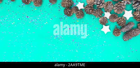 Banner of Colorful holographic foil confetti background wit cones, stars on trendy mint green colored paper. Simple holiday concept. Top view, flat - Stock Photo