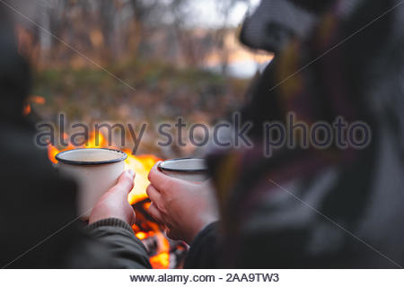 Two people warming hands with hot drinks by the bonfire. Spending nice time outdoors in chilly weather at a camping place - tranquil and peaceful scen - Stock Photo