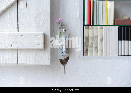 Detail of a small bookshelf with shutter, nicely decorated with a pink aster in a small glass vase - Stock Photo