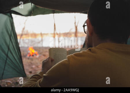 Man sits in tent by the campfire and reads a book. Enjoying quiet peaceful holiday on the nature, the concept of tranquility and getting away from urb Stock Photo