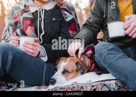 Two people having a lovely time outdoors with a pet in autumn. Man and woman in warm clothes sit outdoors together with their dog on a lovely chilly d
