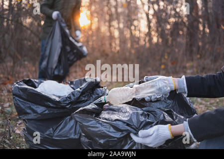 Environmental awareness concept: people clean up forest from plastic waste. Bags full of old bottles and other trash gathered from the nature by a gro Stock Photo