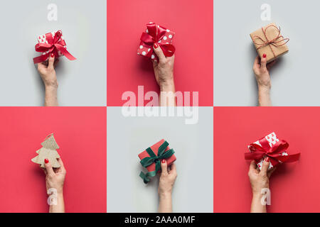 Female hands holding different gifts and Christmas tree on grey. Xmas greeting card. Happy Boxing day. - Stock Photo