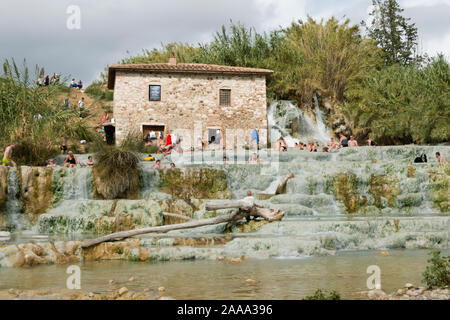 Saturnia, Grosseto / Italy 23 September 2019: Tourist bathing at Natural spa with waterfalls and hot springs Therme di Saturnia in Tuscany. - Stock Photo
