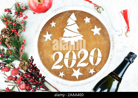 Concept with traditional Greek new year's cake,vasilopita, a bottle of champagne,a class ,a pomegranate,ornaments and lucky charms - Stock Photo