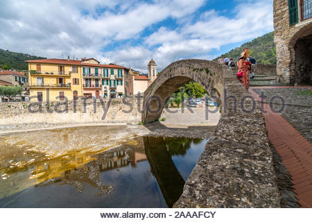 Travelers including a young couple visit the historic Monet bridge at the medieval hilltop village of Dolceacqua, Italy. - Stock Photo