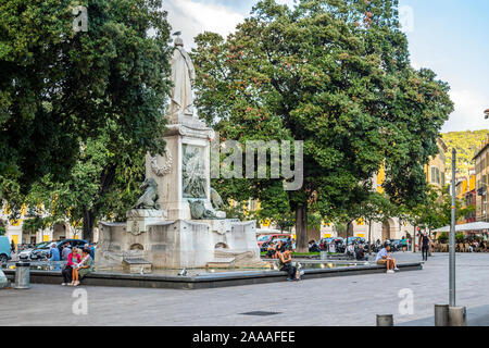 Local French men and women relax at the water fountain and statue in Place Garibaldi in central Nice, France, on the French Riviera - Stock Photo