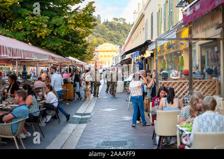 French soldiers in military fatigues patrol the Cours Saleya Old Town area in Nice, France as diners enjoy an early dinner on the French Riviera. - Stock Photo