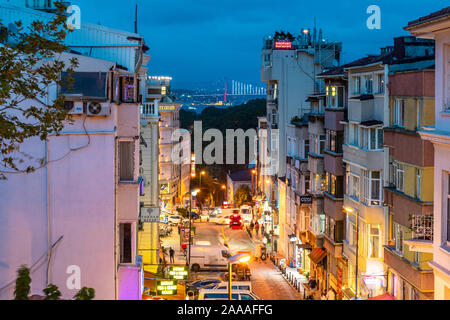 Night view from a upper level window overlooking a busy street in Istanbul, Turkey, with the Bosphorus Bridge illuminated in the distance. - Stock Photo