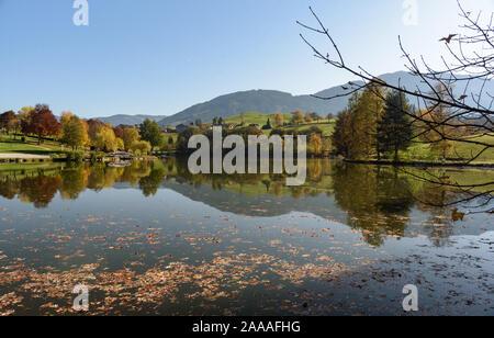 View of Lake Ritzensee on a sunny autumn day in Saalfelden with still reflecting water mountain with clear blue sky. Saalfelden, Pinzgau, Salzburg Lan - Stock Photo