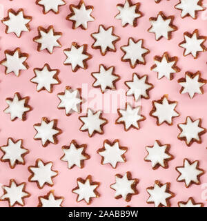 Almond stars biscuits with sugar icing on pink background - seamless pattern - Stock Photo