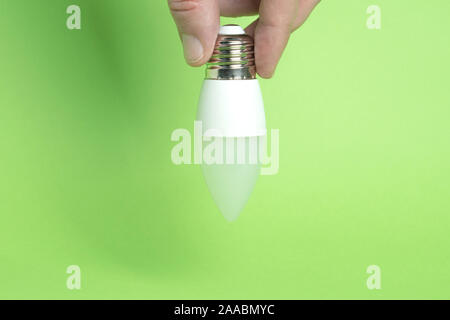 Eco power concept. LED bulb in hand on green background