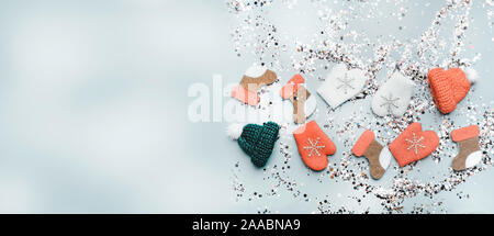 Colorful Sparkling holographic glitter confetti, toy hats, mittens, boots. Christmas Holidays abstract background, toned - Stock Photo