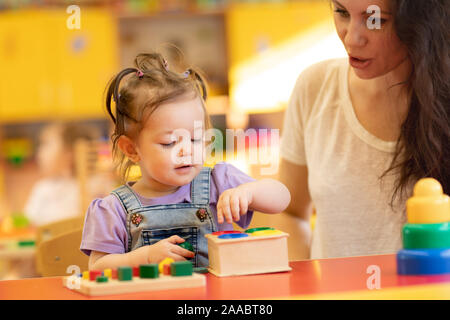 Parent and little kid playing with educational toys, stacking and arranging colorful pieces. Learning through experience concept - Stock Photo