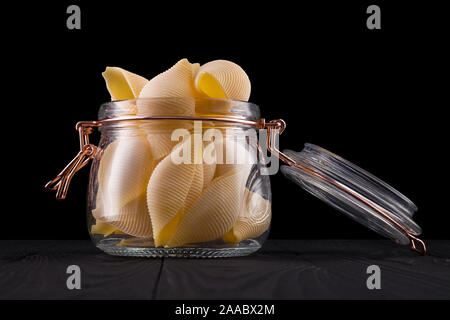Jar of conchiglie pasta shell on wooden table isolated on black background - Stock Photo