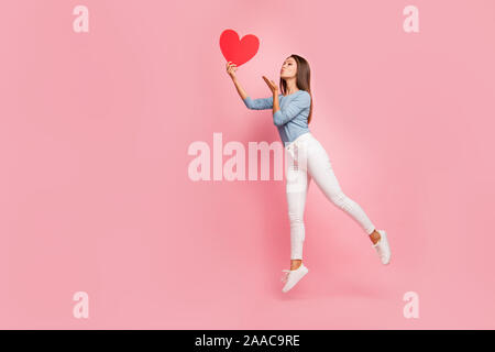 Full length body size side brown haired profile photo of cheerful positive cute pretty nice tender girl sending air kiss to heart held isolated pastel