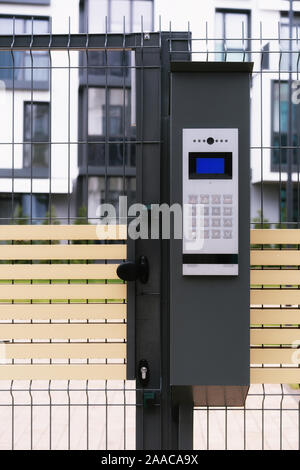 safety in modern residential buildings. fenced yard, closed gate with electronic lock. - Stock Photo