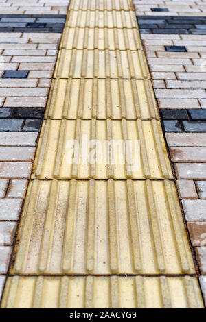 An adapted environment for visually impaired people in a modern city. A special pavement coating is tactile tiles for the disabled. - Stock Photo
