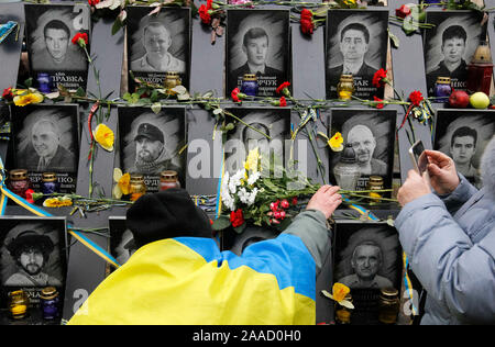A man lays flowers to the memorial of dead Maidan activists (Heroes of the Heavenly Hundred) during the anniversary in Kiev.Ukrainians mark the 6th anniversary of the beginning of the Revolution of Dignity or the Euromaidan Revolution in which more than hundred anti-government protesters died. - Stock Photo