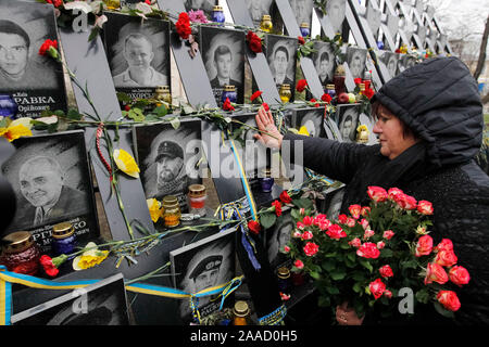 A woman holds flowers at the memorial of dead Maidan activists (Heroes of the Heavenly Hundred) during the anniversary in Kiev.Ukrainians mark the 6th anniversary of the beginning of the Revolution of Dignity or the Euromaidan Revolution in which more than hundred anti-government protesters died. - Stock Photo