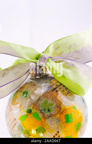 Christmas tree ornament with a green and silver colored bow and the glass decoration is multi colored in green silver white and gold. Copy Space. - Stock Photo