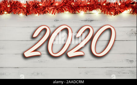 2020 message written below a string of christmas lights and baubles on a distressed white wooden background - Stock Photo