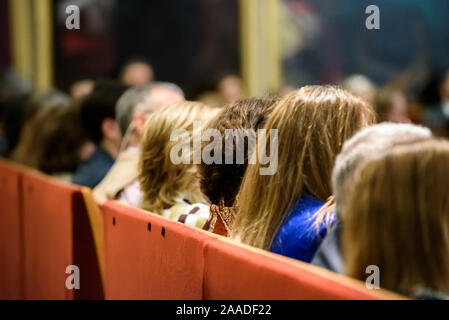 Feminist women attend a talk sitting in a conference room, from behind, unrecognizable. - Stock Photo