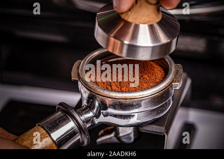 Barista is using a tamper to press freshly ground morning coffee - Stock Photo