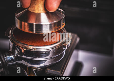 Barista pressing ground coffee into portafilter by tamper to making coffee - Stock Photo