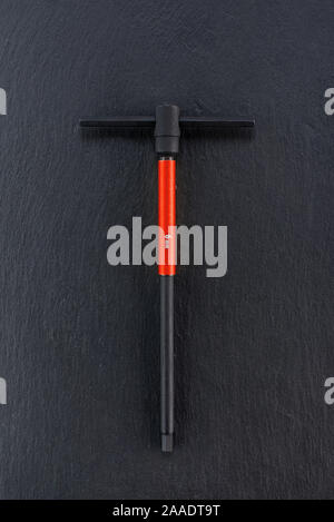 Professional reinforced black matt T-shape wrench placed on a dark background. T-type handle Tool used in a workshop. View from the top. - Stock Photo