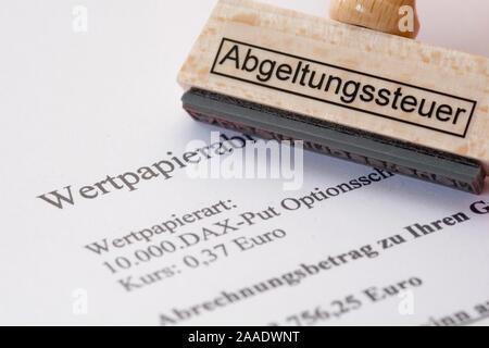 Stempel mit Aufschrift 'Abgeltungssteuer' liegt auf einer Wertpapierabrechnung - Stock Photo