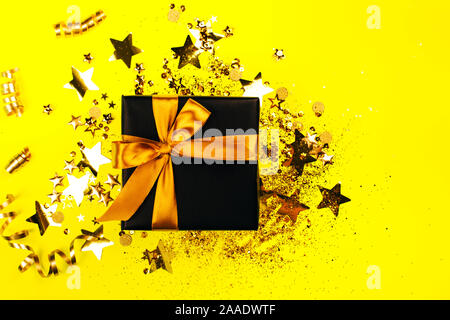 Black gift box with golden bow on yellow background with glitter. Holiday concept. - Stock Photo