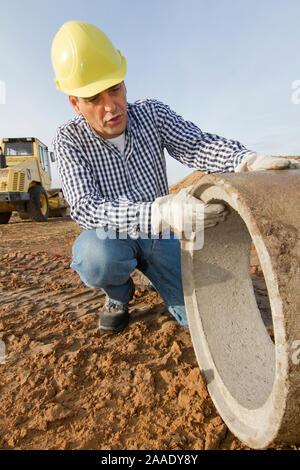 Bauarbeiter arbeitet mit Rohr - Stock Photo