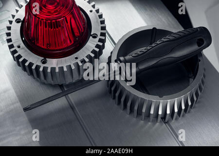 Professional reinforced black matt screw driver placed on a gearwheel. View from the top. - Stock Photo