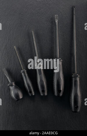 Professional reinforced black matt screw drivers placed on a dark ground. View from the top. - Stock Photo