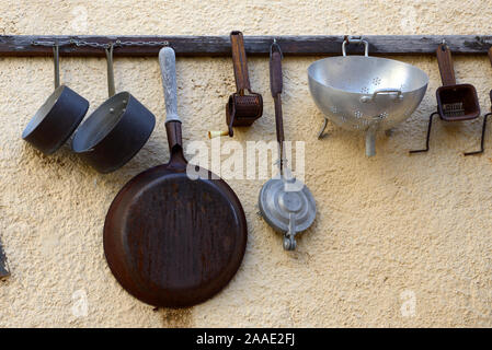 Vintage or Antique Collection of Old Kitchen Utensils Hanging on Wall Rack including Pans, Drainers & Spatulas - Stock Photo
