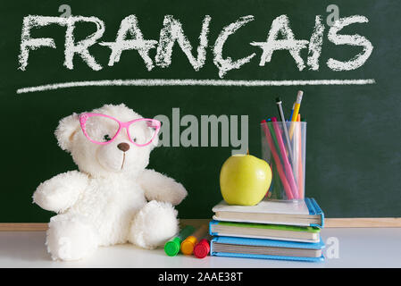 Teddy bear wearing glasses in a French language classroom next to an apple and a pile of books and a dictionary against a blackboard. - Stock Photo