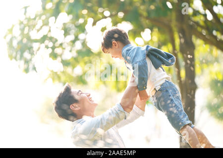 cute little asian boy lifted by father outdoors in park - Stock Photo