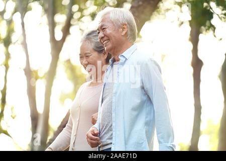 happy senior asian couple walking talking relaxing outdoors in park