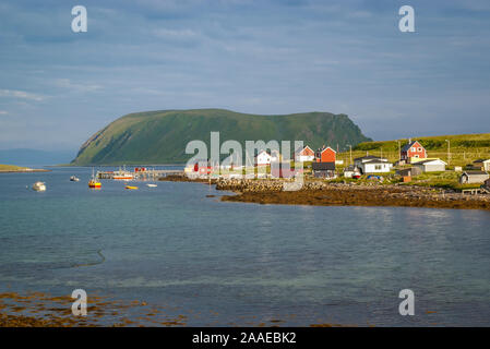 Summer view of a small fishing village with traditional, colorful wooden houses in a quiet and calm bay of the Barents Sea above the arctic circle. - Stock Photo