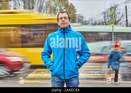 A sad middle-aged man, over 50 years old, dressed in a blue jacket, stands in front of a pedestrian crossing with his hands in pockets, probably he is - Stock Photo