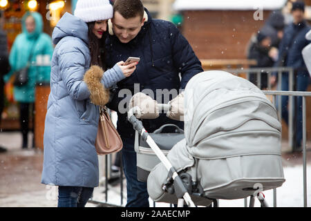 Lviv, Ukraine - January 4, 2019: young family mother with father and child in baby carriage outdoors at winter day - Stock Photo